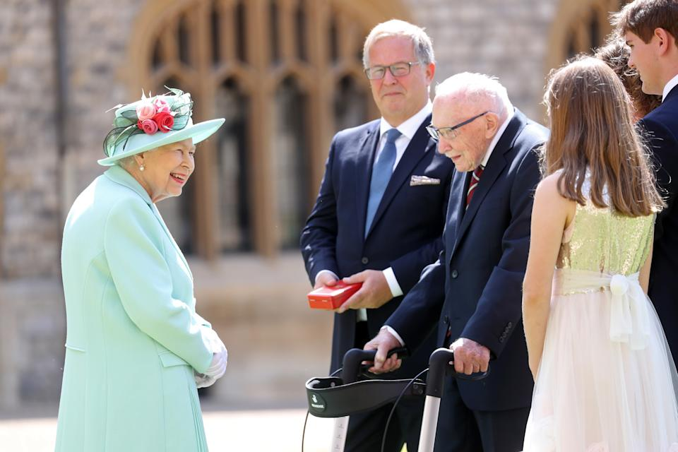 WINDSOR, ENGLAND - JULY 17: Queen Elizabeth II talks Captain Sir Thomas Moore and his family after awarding him with the insignia of Knight Bachelor at Windsor Castle on July 17, 2020 in Windsor, England. British World War II veteran Captain Tom Moore raised over £32 million for the NHS during the coronavirus pandemic.  (Photo by Chris Jackson/Getty Images)