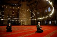Staff at Suleymaniye Mosque perform a morning prayer behind closed doors during the first day of Eid and the second day of a four-day curfew, amid the coronavirus disease (COVID-19) outbreak, in Istanbul, Turkey May 24, 2020. REUTERS/Umit Bektas TPX IMAGES OF THE DAY