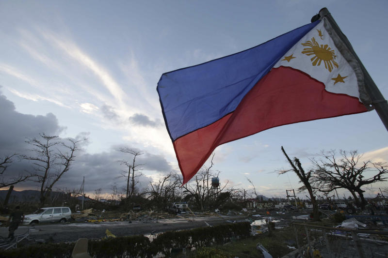 FILE - In this Saturday, Nov. 9, 2013 file photo, a Philippine flag stands amongst the damage caused after powerful Typhoon Haiyan slammed into Tacloban city, Leyte province, central Philippines. Haiyan slammed the island nation with a storm surge two stories high and some of the highest winds ever measured in a tropical cyclone. An untold number of homes were blown away, and thousands of people are feared dead. (AP Photo/Aaron Favila, File)