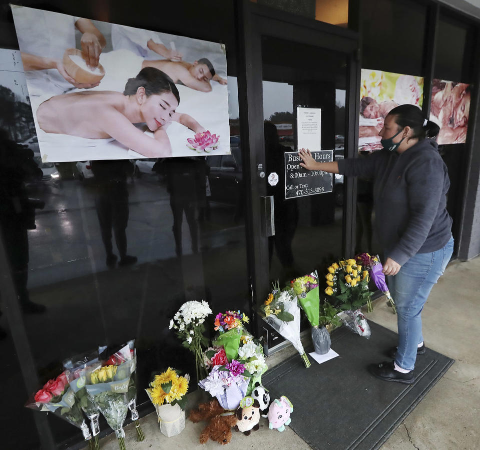 Jessica Lang pauses and places her hand on the door in a moment of grief after dropping off flowers at Youngs Asian Massage parlor where four people were killed, Wednesday, March 17, 2021, in Acworth, Ga. Lang, a local resident who lives nearby, said she knew one of the victims. A white gunman was charged Wednesday with killing eight people at three Atlanta-area massage parlors on Tuesday in an attack that sent terror through the Asian American community that's increasingly been targeted during the coronavirus pandemic. (Curtis Compton/Atlanta Journal-Constitution via AP)
