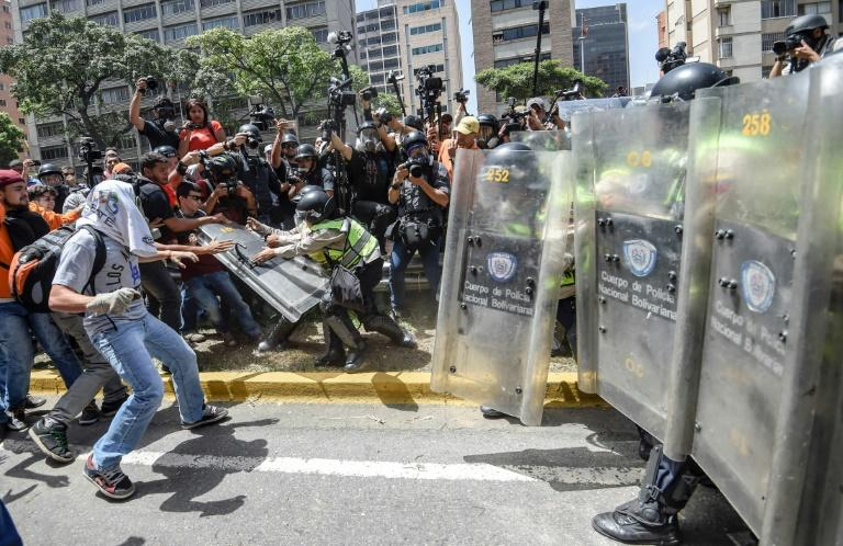 Protesters hurled stones at riot police, who fired tear gas as they blocked them from marching through central Caracas, Venezuela