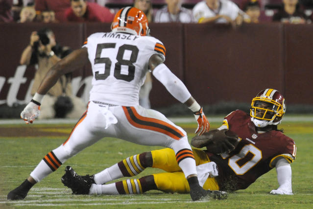 Washington Redskins quarterback Robert Griffin III (10) slides down in front of Cleveland Browns outside linebacker Christian Kirksey (58) during the first half of an NFL preseason football game Monday, Aug. 18, 2014, in Landover, Md. (AP Photo/Richard Lipski)
