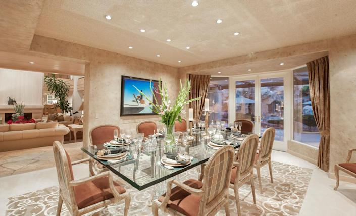 """<p>The formal dining room opens onto the patio and pool area. (All photos via <a href=""""http://bit.ly/1OjQdjg"""" rel=""""nofollow noopener"""" target=""""_blank"""" data-ylk=""""slk:Concierge Auctions listing"""" class=""""link rapid-noclick-resp"""">Concierge Auctions listing</a>)</p>"""