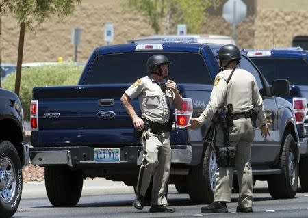 Metro Police officers confer outside a Wal-mart after a shooting in Las Vegas June 8, 2014. REUTERS/Las Vegas Sun/Steve Marcus