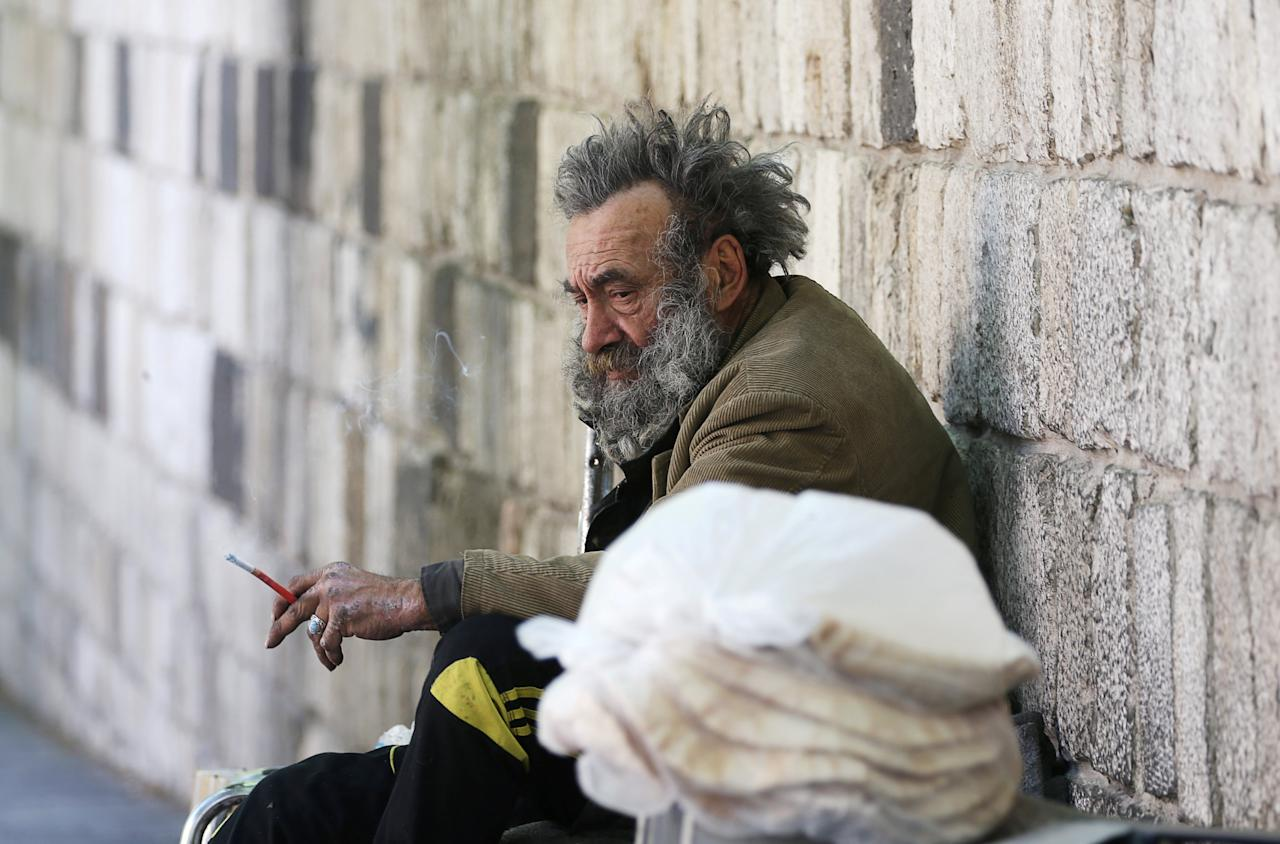 A homeless man sits as he holds a cigarette in Damascus, Syria April 21, 2018. REUTERS/Ali Hashisho