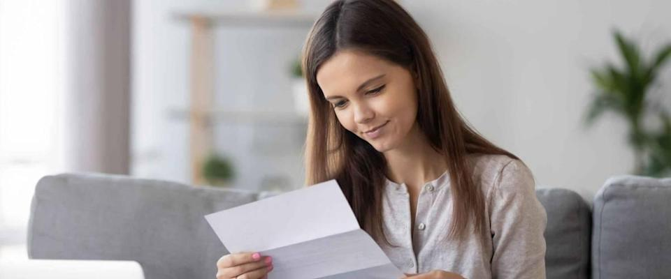 Young woman sitting on sofa at home holds paper reading letter looks happy