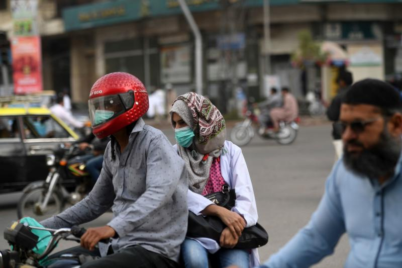 Commuters wear face masks on a street in Karachi on February 28, 2020 as Pakistan has detected its first two cases of novel coronavirus. - Pakistani authorities were scrambling on February 27 to screen hundreds of people who had recently arrived from Iran, which has emerged as a major hotspot for coronavirus, after Islamabad confirmed its first two infections. (Photo by Asif HASSAN / AFP) (Photo by ASIF HASSAN/AFP via Getty Images)