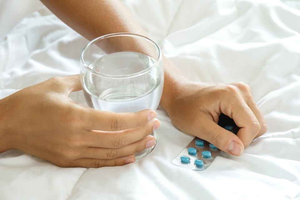 Female hands with a glass of water and blister pack with pills