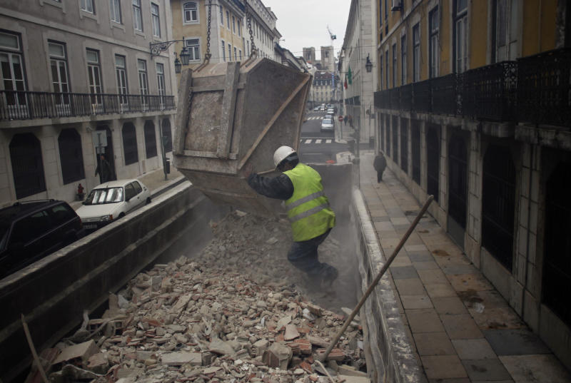 A construction worker empties a truck with debris next to the Bank of Portugal headquarters in Lisbon, Wednesday, Jan. 8, 2014. Glimmers of hope emerged Wednesday for the eurozone economy to suggest that the coming year will see the recovery gathering steam. Eurostat, the EU's statistics office, said the eurozone's unemployment rate held steady in November at a record 12.1 percent for the eighth month running after a modest 4.000 rise in the ranks of the jobless to 19.24 million. (AP Photo/Francisco Seco)
