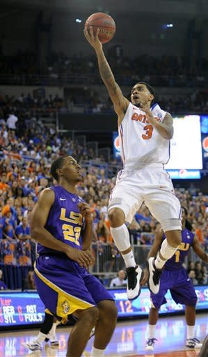 Florida's Mike Rosario (3) goes to the basket with LSU's Raiston Turner (22) unable to block the shot during the first half of an NCAA college basketball game in Gainesville, Fla., Saturday, Jan. 21, 2012. (AP Photo/Phil Sandlin)