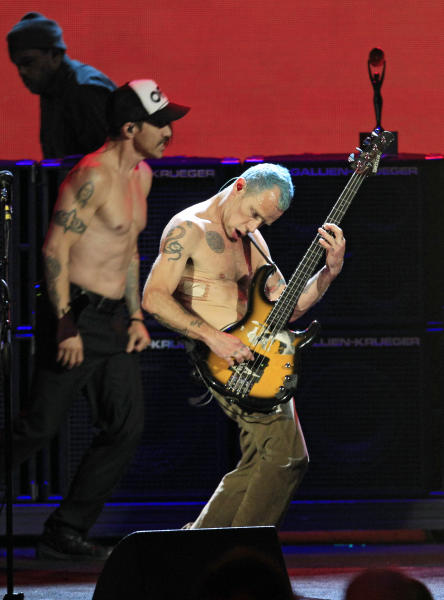 """Red Hot Chili Peppers' Mike """"Flea"""" Balazary, front and Anthony Kiedis perform after induction into the Rock and Roll Hall of Fame Sunday, April 15, 2012, in Cleveland. (AP Photo/Tony Dejak)"""