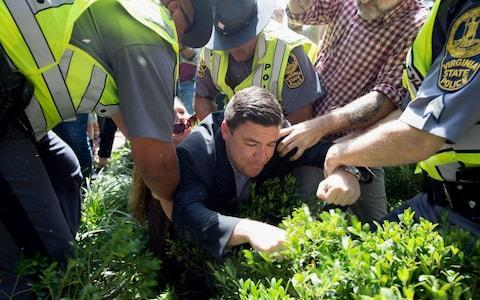Jason Kessler falls into bushes, as he is rushed away from the disrupted press conference at City Hall - Credit: EPA