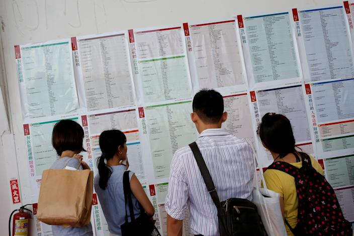 Job seekers look at job information at an employment fair in Taipei, Taiwan on May 28, 2016.