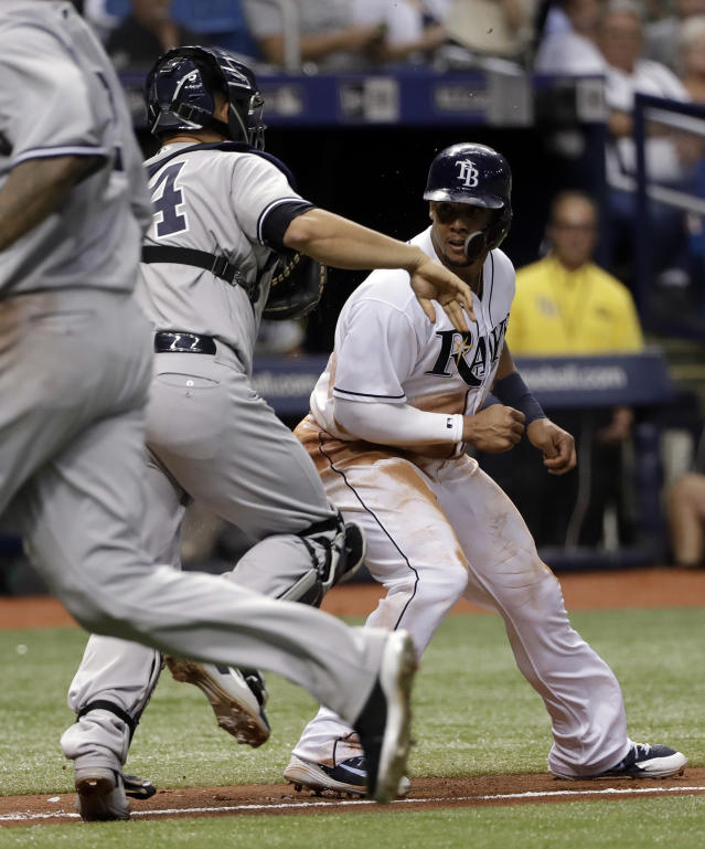 New York Yankees catcher Gary Sanchez (24) tags out Tampa Bay Rays' Carlos Gomez, right, after Gomez was caught in a rundown on a fielder's choice during the fourth inning of a baseball game Friday, June 22, 2018, in St. Petersburg, Fla. (AP Photo/Chris O'Meara)