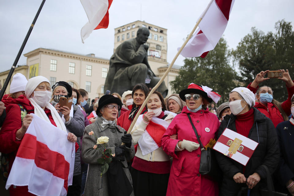 People, most of them pensioners, hold old Belarusian national flags march during an opposition rally to protest the official presidential election results in Minsk, Russia, Monday, Oct. 26, 2020. Factory workers, students and business owners in Belarus have started a general strike, calling for authoritarian President Alexander Lukashenko to resign after more than two months of mass protests triggered by a disputed election. (AP Photo)