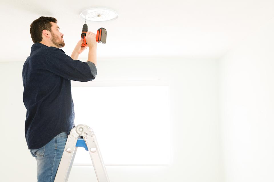Handsome handyman installing a new light fixture with an electric drill. Young man in his 30s doing home renovations