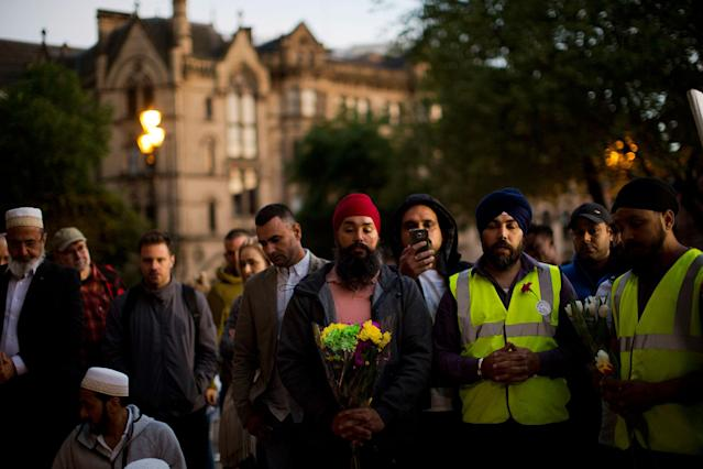 <p>People pray after a vigil in Albert Square, Manchester, England, Tuesday May 23, 2017, the day after the suicide attack at an Ariana Grande concert that left 22 people dead as it ended on Monday night. (AP Photo/Emilio Morenatti) </p>