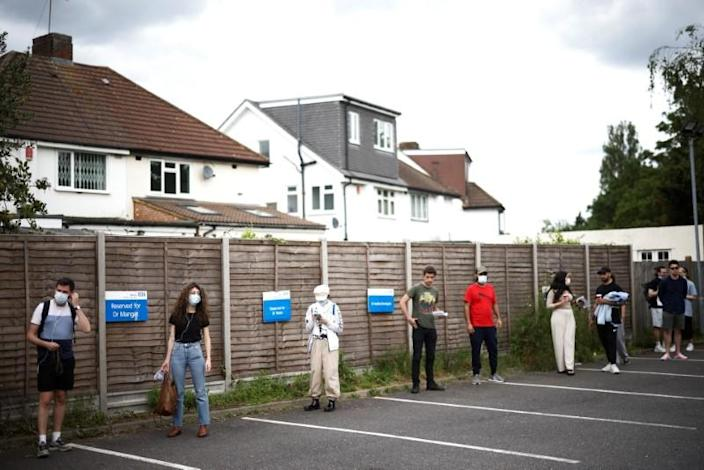 People queue outside a vaccination centre for those aged over 18 at the Belmont Health Centre in Harrow, amid the coronavirus disease (COVID-19) outbreak, in London