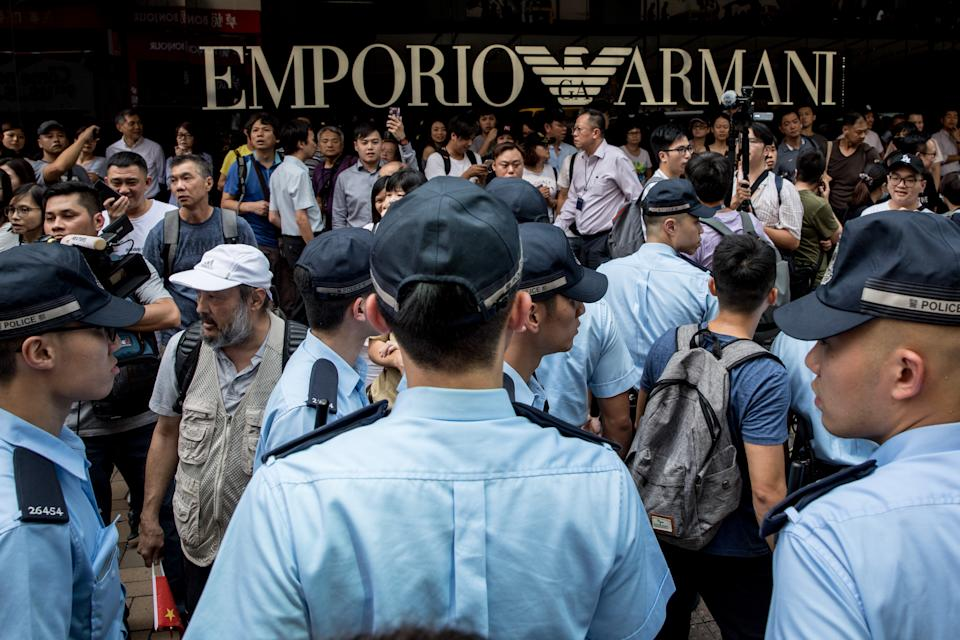 """HONG KONG, CHINA - SEPTEMBER 18: Pro-Democracy supporters (back) shout slogans as police help to escort a small number of pro-China supporters away, after they tried to hold a march outside a shopping mall on September 18, 2019 in Hong Kong, China. Pro-democracy protesters have continued demonstrations across Hong Kong, calling for the city's Chief Executive Carrie Lam to immediately meet the rest of their demands, including an independent inquiry into police brutality, the retraction of the word """"riot"""" to describe the rallies, and genuine universal suffrage, as the territory faces a leadership crisis. (Photo by Chris McGrath/Getty Images)"""