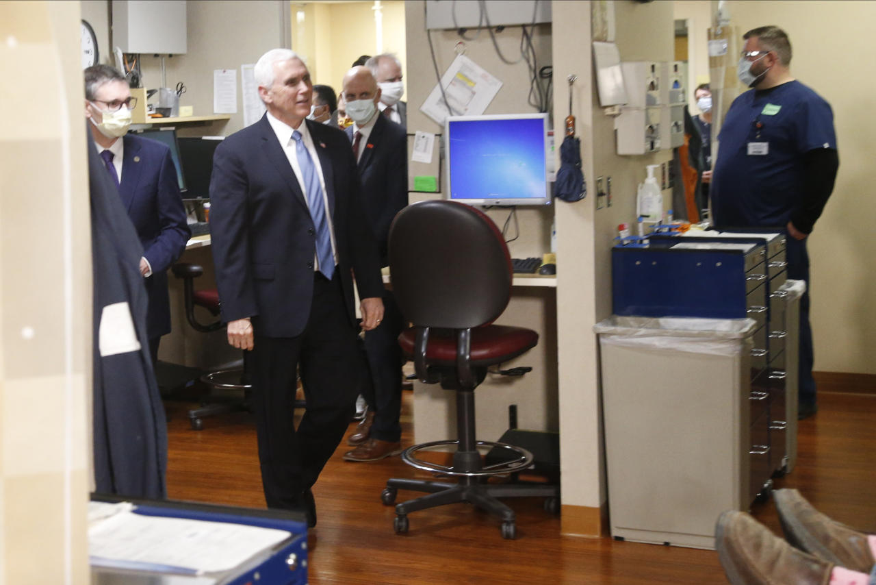 Vice President Mike Pence, left, visits the Mayo Clinic Tuesday, April 28, 2020, in Rochester, Minn., where he toured the facilities supporting COVID-19 research and treatment. Pence chose not to wear a face mask while touring the Mayo Clinic in Minnesota. It's an apparent violation of the world-renowned medical center's policy requiring them. (AP Photo/Jim Mone)