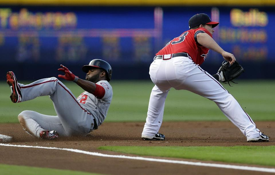 Washington Nationals' Denard Span (2) is safe at third base with a triple as Atlanta Braves third baseman Chris Johnson, right, waits for the throw in the first inning of a baseball game in Atlanta, Friday, May 31, 2013. (AP Photo/John Bazemore)
