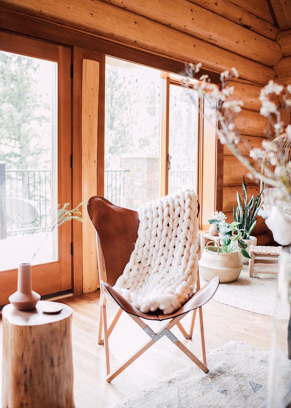 """The four-bedroom family home rests on a plot of seven acres of gorgeous mountain land, Kula tells MyDomaine. """"It's a true log cabin, with logs for just about all the interior walls, and an incredible basement that has been converted into a fully functioning wet bar and wine cave,"""" she explains."""