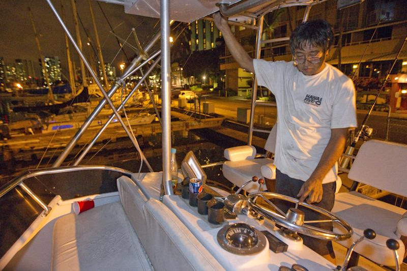 Mike Nakamoto of Honolulu prepare's his client's boat moored at the Ala Wai Harbor to take it to deep water after learning of a tsunami warning Saturday, Oct. 27, 2012, in Honolulu. A tsunami warning has been issued for Hawaii after a 7.7-magnitude earthquake rocked an island off the west coast of Canada. The Pacific Tsunami Warning Center originally said there was no threat to the islands, but a warning was issued later Saturday and remains in effect until 7 p.m. Sunday. A small craft advisory is in effect until Sunday morning.(AP Photo/Eugene Tanner)