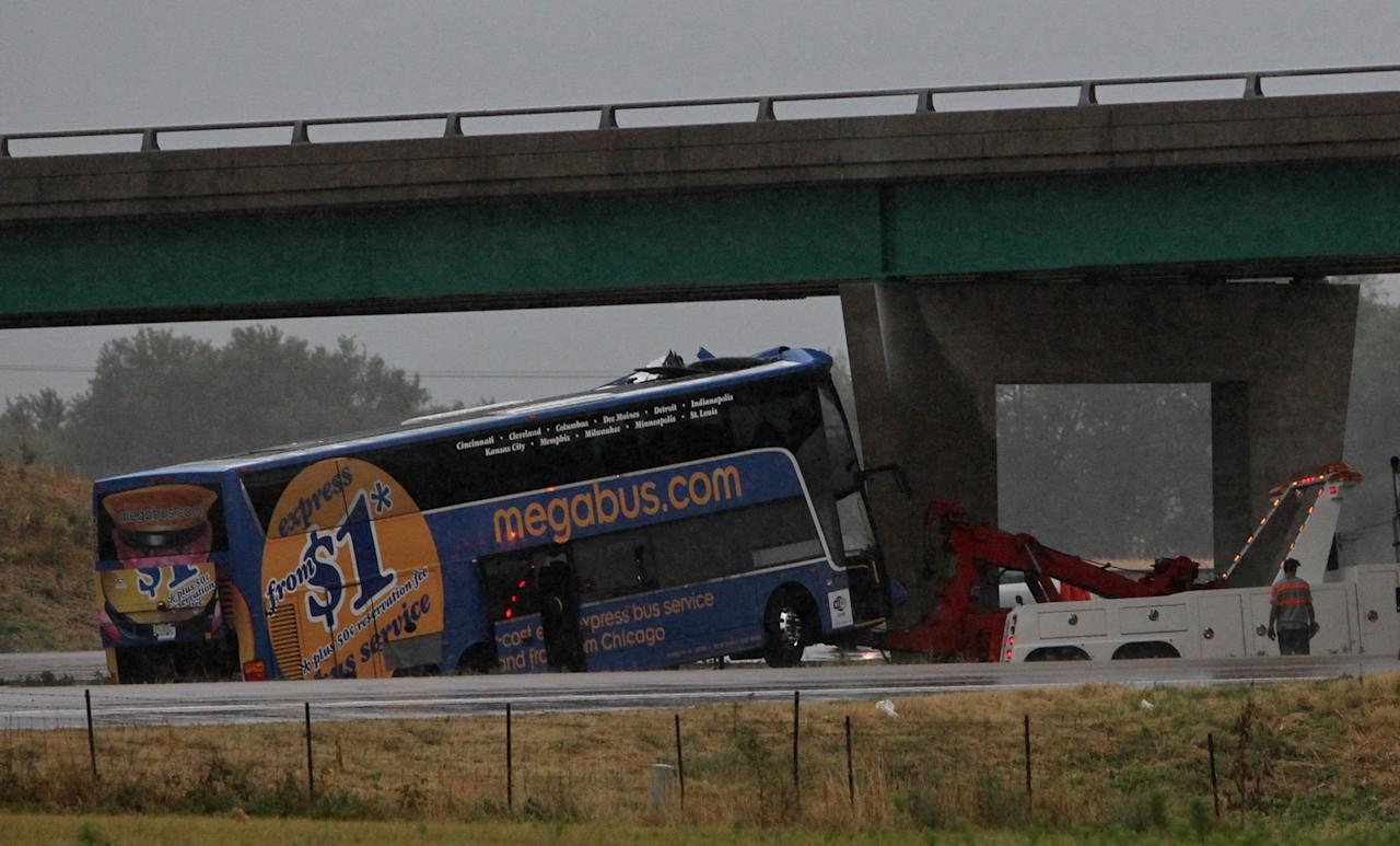 The Megabus is pulled away from the bridge support Thursday evening Aug. 2, 2012 on southbound Interstate 55 north of Litchfield, Ill. The packed double-decker Megabus slammed into an Illinois interstate bridge support pillar Thursday, hurtling screaming passengers from their seats and leaving at least one person dead and more than three dozen injured, officials said. (AP Photo/St. Louis Post-Dispatch, J.B. Forbes)