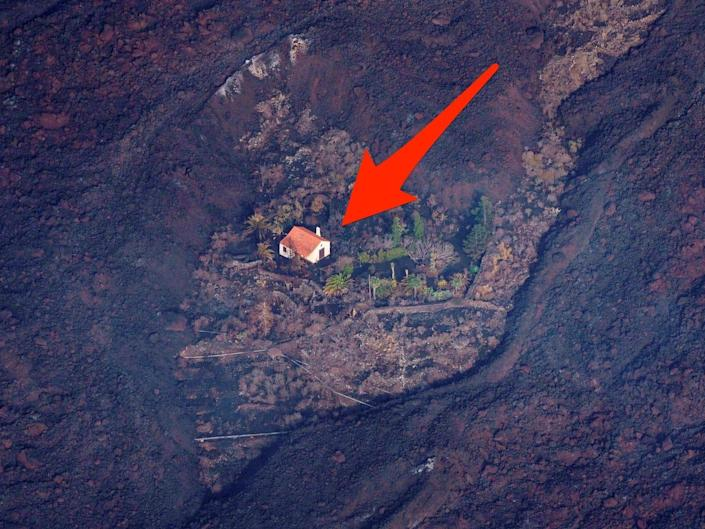 an arrow points to a house surrounded by earth scorched by the lava from the Cumbre Vieja violcano eruption on La Palma island