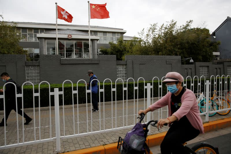 People travel past Chinese and Hong Kong flags in Beijing