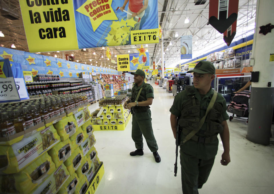 FILE - In this Jan. 11, 2009 file photo, soldiers check prices at a supermarket accused by the government of raising prices in Caracas, Venezuela. In a country riven by political strife, Venezuela's military has often been one of the few unifying forces keeping tempers at bay. Generals have stepped in to deflate coups and other national crises, while soldiers have been dispatched to run services from food distribution to oil production. (AP Photo/Fernando Llano, File)