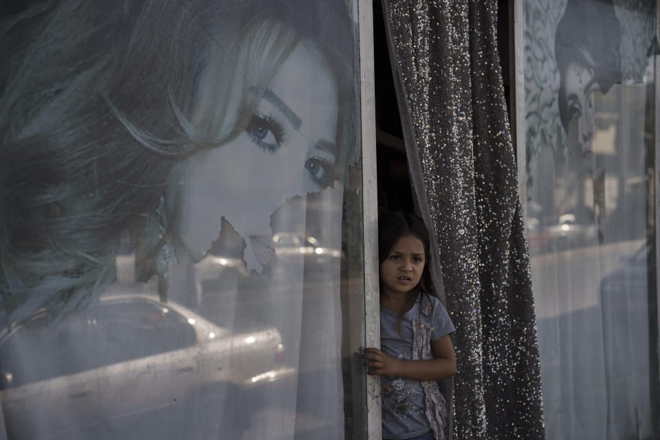 An Afghan girl looks out from a beauty salon in Kabul, Afghanistan, Thursday, Sept. 16, 2021. Since the Taliban gained control of Kabul, several images depicting women outside beauty salons have been removed or covered up. (AP Photo/Felipe Dana)