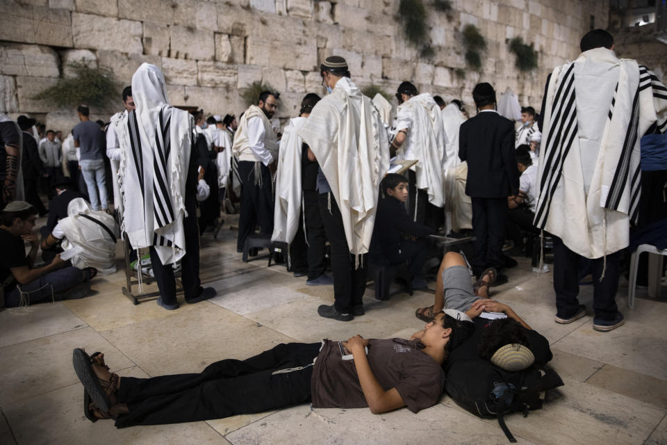 Ultra-Orthodox Jewish men pray as others sleep during the mourning ritual of Tisha B'Av (Ninth of Av) fasting and a memorial day, commemorating the destruction of ancient Jerusalem temples at the Western Wall, the holiest site where Jews can pray in the Old City of Jerusalem, Sunday, July 18, 2021. (AP Photo/Oded Balilty)