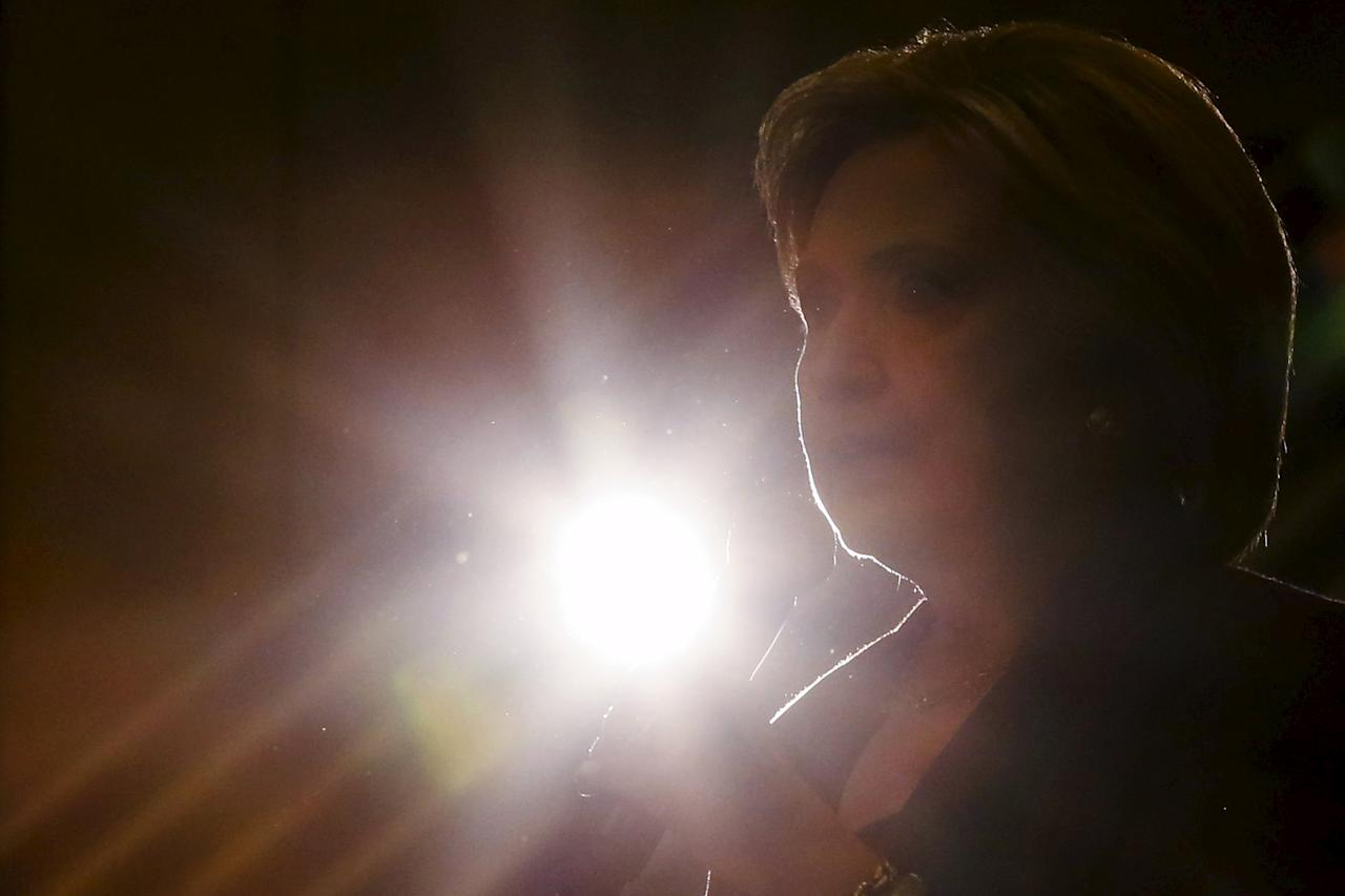 U.S. Democratic presidential candidate Hillary Clinton is backlit by spotlight while speaking during a campaign rally at Winnacunnet High School in Hampton, New Hampshire