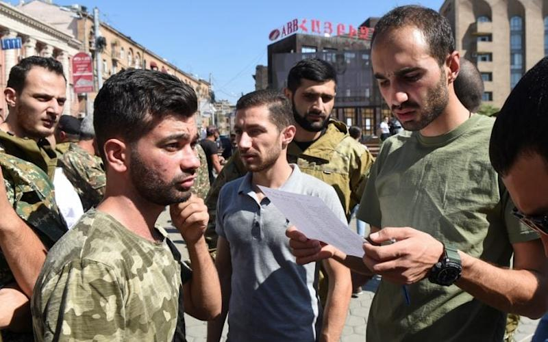 Men attend a meeting to recruit military volunteers after Armenian authorities declared martial law and mobilised its male population following clashes with Azerbaijan over the breakaway Nagorno-Karabakh region - Melik Baghdasaryan