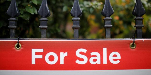 A real estate sign is seen hanging on a fence in front of a house for sale in Ottawa, Aug. 15, 2017.