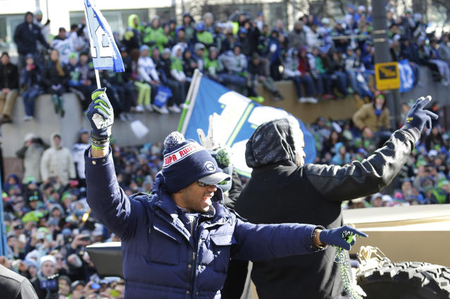 Seattle Seahawks quarterback Russell Wilson points to fans during the Super Bowl champions parade on Wednesday, Feb. 5, 2014, in Seattle. The Seahawks beat the Denver Broncos 43-8 in NFL football's Super Bowl XLVIII on Sunday. (AP Photo/Ted S. Warren)