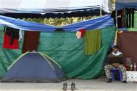 An anti-government protester takes a rest beside his tent during a rally near the Government Complex in Bangkok January 24, 2014. REUTERS/Chaiwat Subprasom