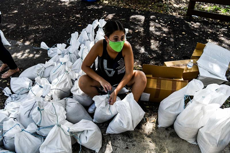 A woman prepares sand bags for distribution to the residents of Palmetto Bay near Miami (AFP via Getty Images)