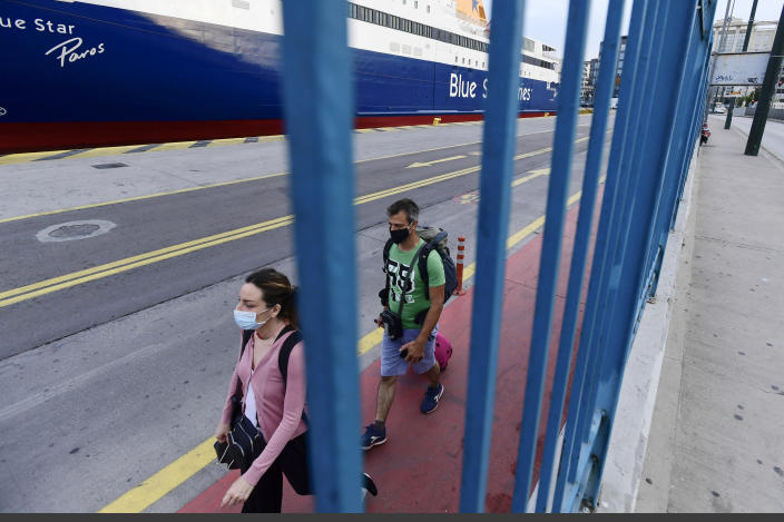 Passengers make their way during a 24-hour labour strike at the port of Piraeus, near Athens, Thursday, June 10, 2021. Greece's biggest labor unions stage a 24-hour strike to protest a draft labor bill being debated in parliament, which workers say will erode their rights. (AP Photo/Michael Varaklas)