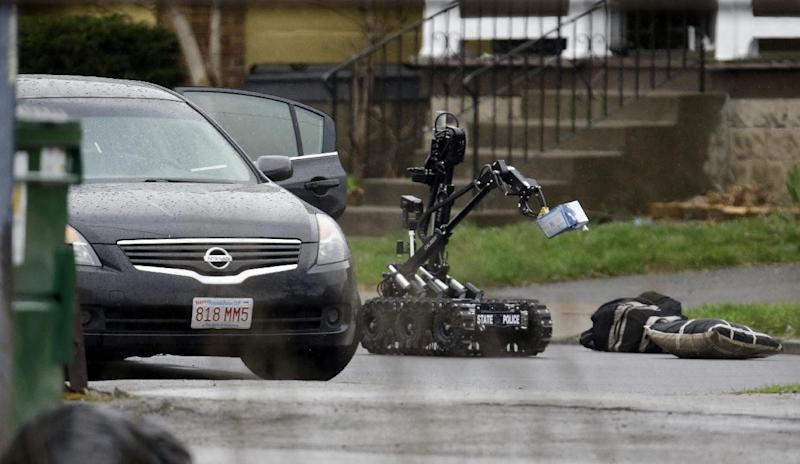 A New York State Police robot removes suspicious packages from a car in Niagara Falls, N.Y., Friday, April 19, 2013. Trooper Jeffrey Bebak says that a state police bomb disposal team is using a robot to remove items from the car that was stopped earlier in the morning. Bebak says two men are being questioned by police but he has no other details. The response came amid an intense manhunt in Massachusetts one of the Boston Marathon bombers. (AP Photo/David Duprey)
