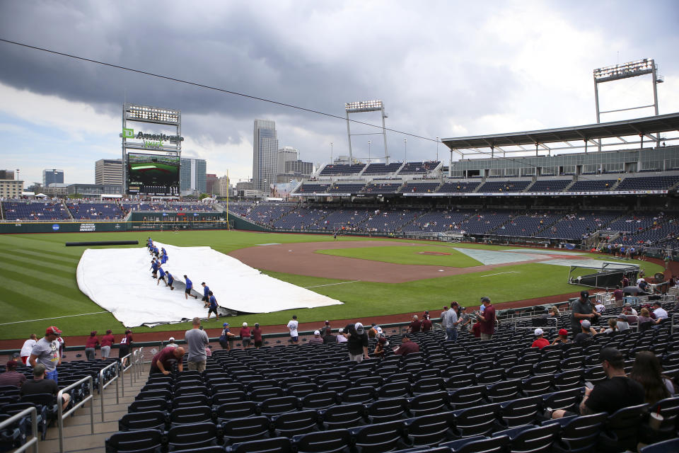 Grounds crew members remove the tarp on the infield before Game 2 of the NCAA College World Series baseball finals between Mississippi State and Vanderbilt, Tuesday, June 29, 2021, in Omaha, Neb. (AP Photo/John Peterson)