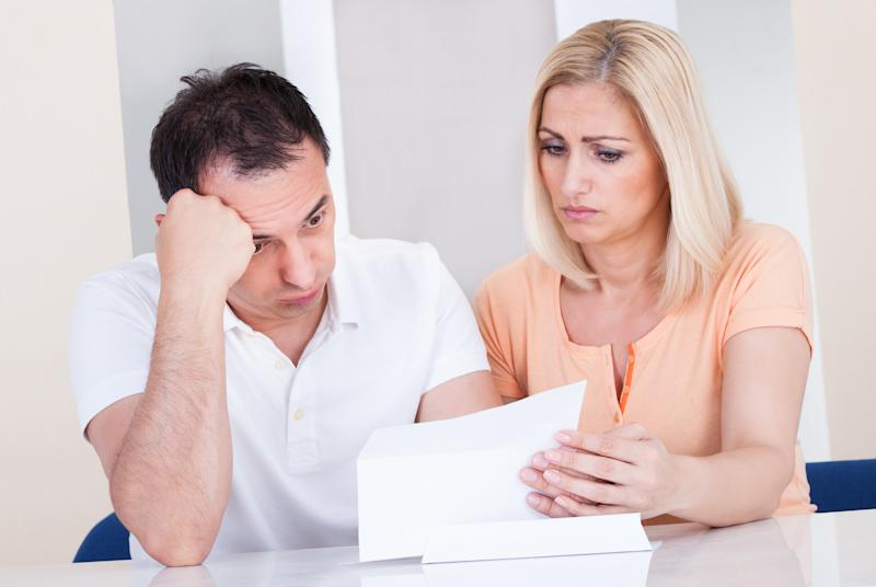Couple with unhappy expressions looking at document