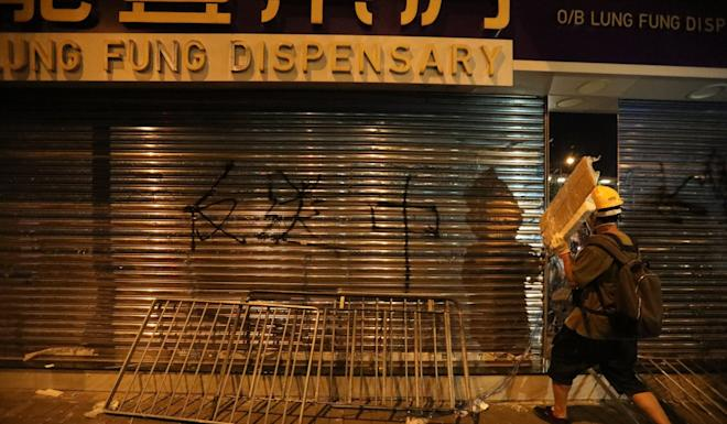 Graffiti is spray-painted on the shutters of a Sheung Shui pharmacy. Photo: Felix Wong