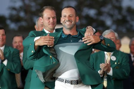 Sergio Garcia of Spain is presented the green jacket by last year's champion, Danny Willett of England, after Garcia won the 2017 Masters golf tournament in a playoff at Augusta National Golf Club in Augusta, Georgia, U.S., April 9, 2017. REUTERS/Brian Snyder