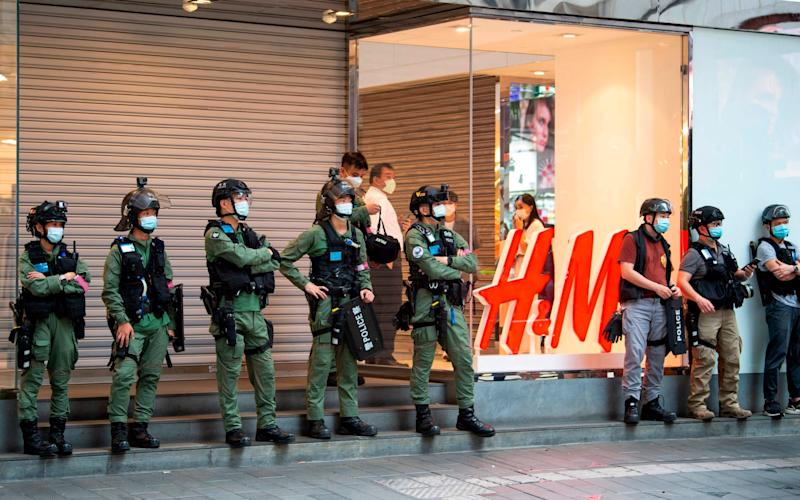 Police officers stand guard in front of a closed clothing store in Causeway Bay during a protest on China's National Day, - Jayne Russell/AFP