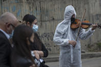 Violinist Antonio Hernandez plays for the relatives of COVID-19 victim Miryam Rodriguez, while they are gathered for prayer by the hearse that carries her remains to Serafin Cemetery, before cremation in Bogota, Colombia, Friday, June 18, 2021. Due to regulations to contain the new coronavirus, relatives cannot enter the cemetery. (AP Photo/Ivan Valencia)