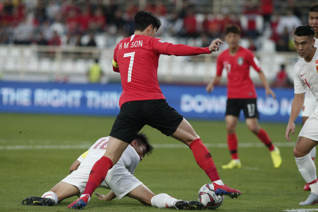 China's defender Zheng Zhi, ground, and South Korea's forward Son Heung-Min fight for the ball during the AFC Asian Cup group C soccer match between South Korea and China at Al Nahyan Stadium in Abu Dhabi, United Arab Emirates, Wednesday, Jan. 16, 2019. (AP Photo/Nariman El-Mofty)