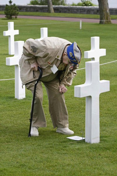 U.S. WW II veteran Clarence Mac Evans, 87, from West Virginia, who landed in Normandy on June 6, 1944, with the 29th infantry division, leans on the tomb of comrade Franck Nuzzo, from the 29th division who died on June 6, 1944, at the Colleville American military cemetery.(AP Photo/Remy de la Mauviniere)