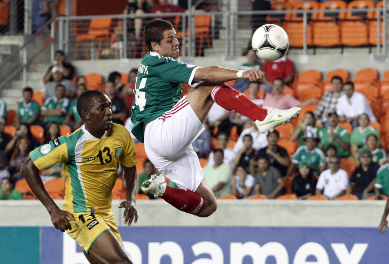 Javier Hernandez of Mexico takes a shot at the goal past Charles Pollard (L) of Guyana during their 2014 World Cup qualifying soccer match in Houston October 12, 2012. REUTERS/Richard Carson (UNITED STATES - Tags: SPORT SOCCER TPX IMAGES OF THE DAY)